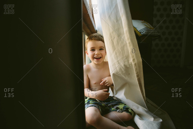 Happy young boy playing behind curtain