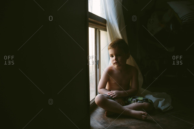 Portrait of a young boy sitting on floor by window