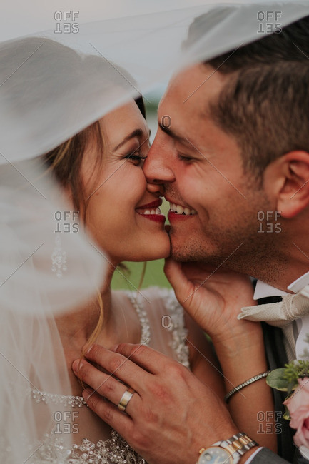 Newly married couple smiling and kissing beneath the bride's veil