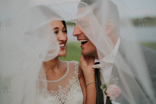 Newly married couple laughing and touching as they stand under her veil