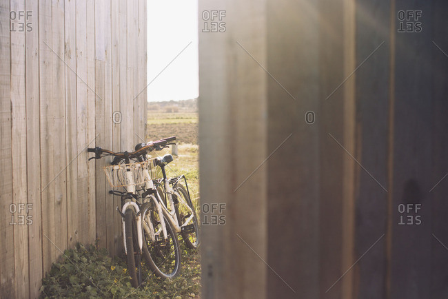 Pair of bicycles leaning against wooden fence