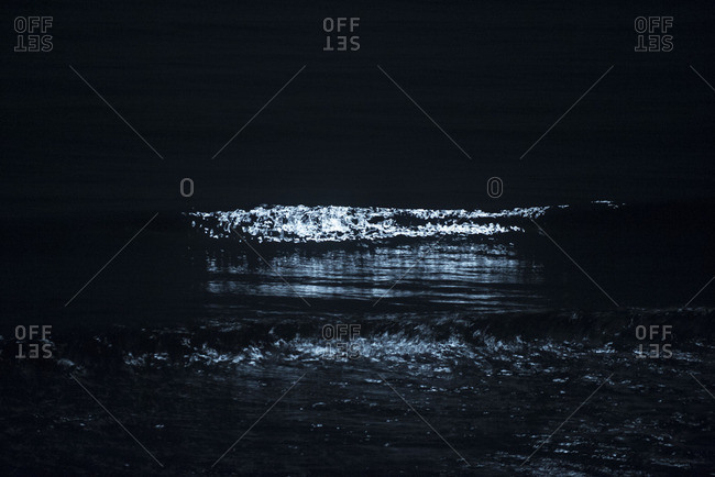 Moonlight reflecting on ocean waves at night