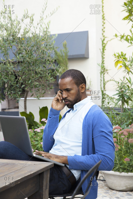 Man making phone call while using laptop computer outdoors