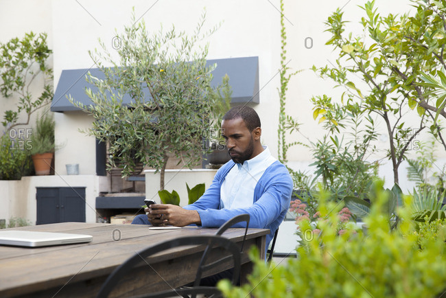 Man seated at table in hotel courtyard using cell phone