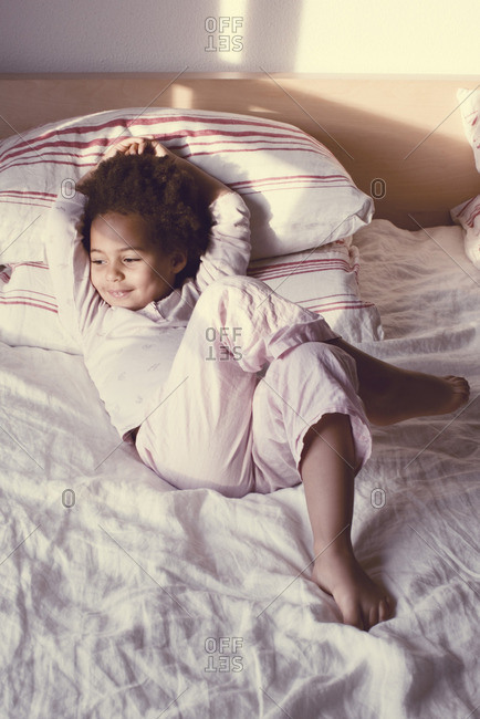 Little girl lying on bed in pajamas
