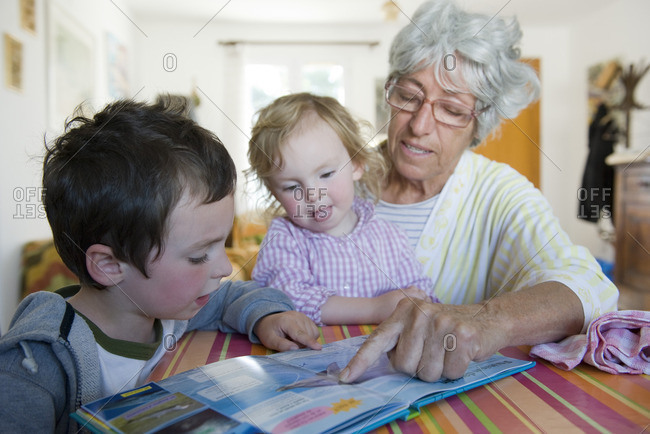 Grandmother reading book with young grandchildren