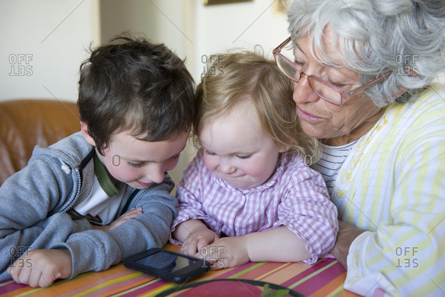 Grandmother and young grandchildren looking at cell phone together