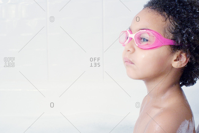 Little girl with swimming goggles in bath