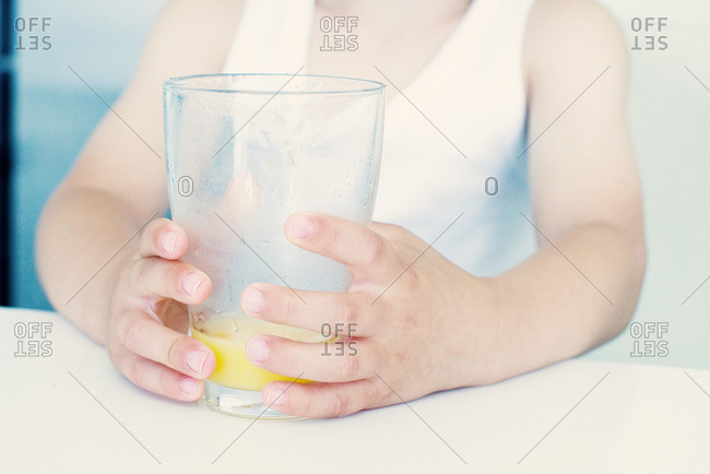 Little girl holding glass with juice, mid section
