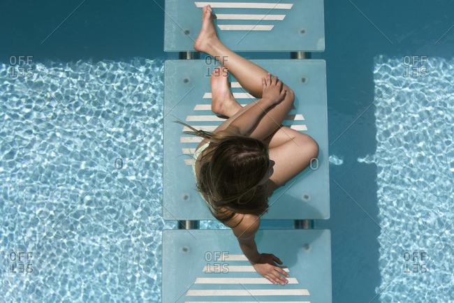 Woman relaxing on swimming pool footbridge