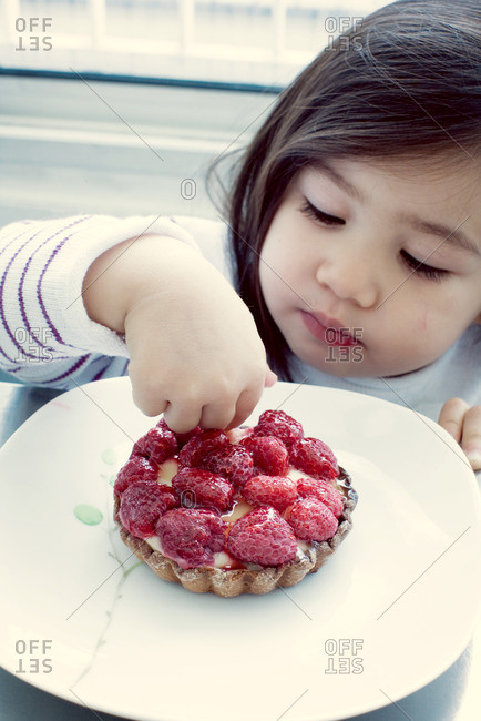 Little girl picking at raspberry tart
