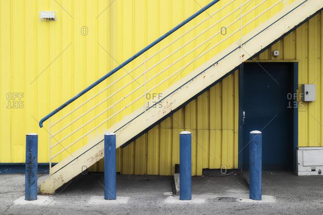 Yellow building, blue bollards