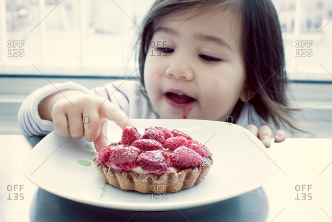 Little girl getting taste of raspberry tart
