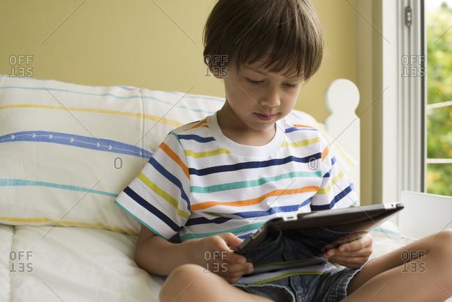 Boy sitting on bed, using digital tablet
