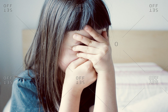 Girl covering face with hands