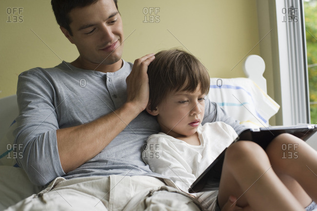 Father and son relaxing together with electronic book