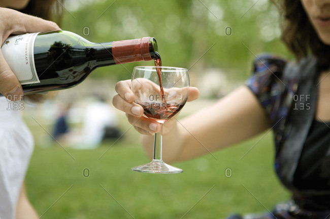 Pouring glass of red wine outdoors
