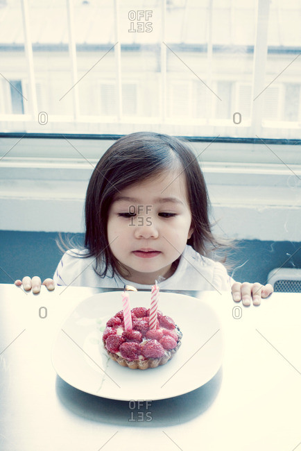 Little girl blowing out candles on birthday cake