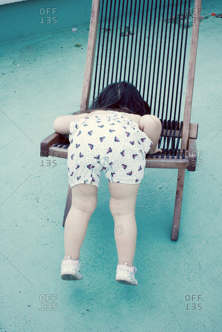 Little girl climbing onto chair, rear view