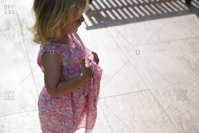 Little girl standing outdoors, looking away in thought