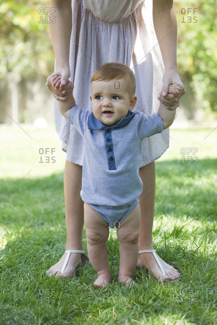 Baby standing outdoors, holding mother\'s hands for support