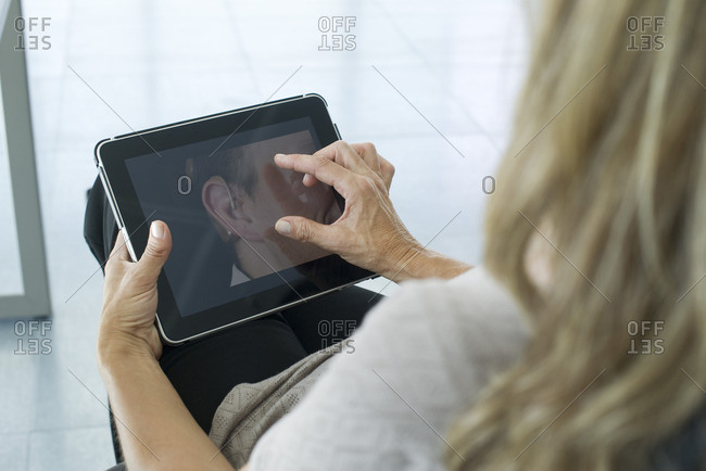 Woman using digital tablet, over the shoulder view