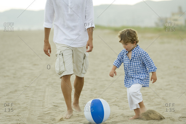 Father and son playing with ball at the beach