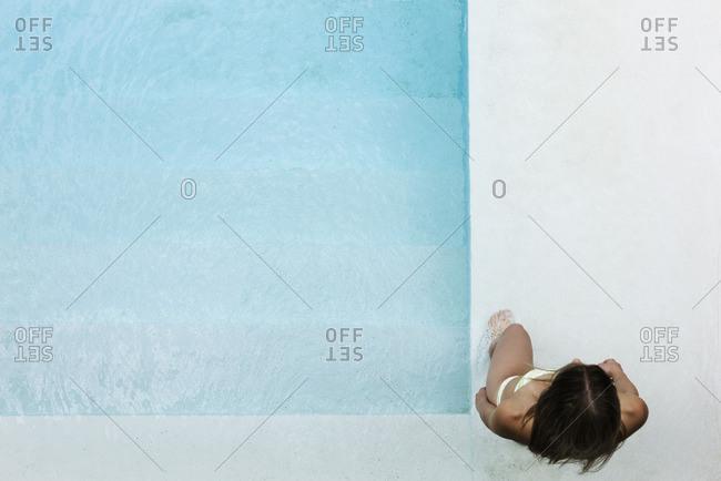 Woman wading into pool