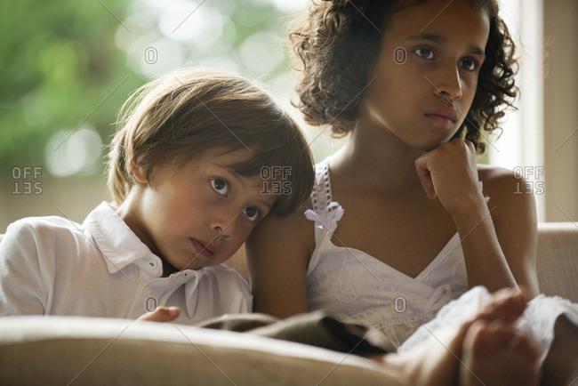 Children watching TV together, boy resting head on sister's shoulder