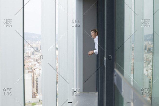 Woman looking out of office window at view of city