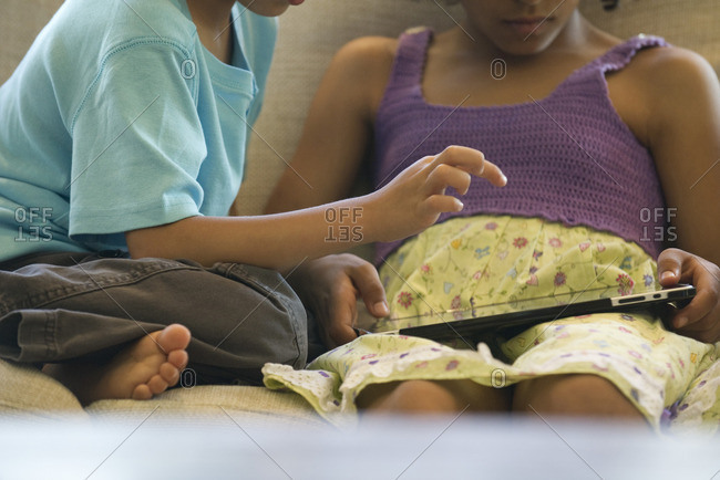 Children using digital tablet, cropped