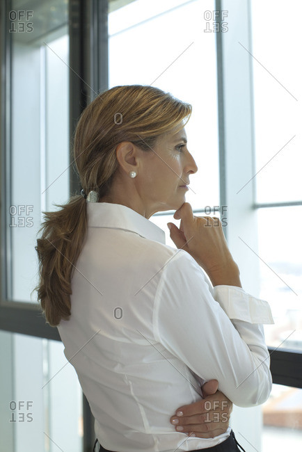 Businesswoman looking out of window with hand under chin
