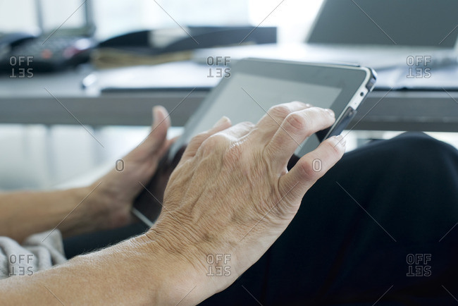 Woman's hand touching digital tablet screen