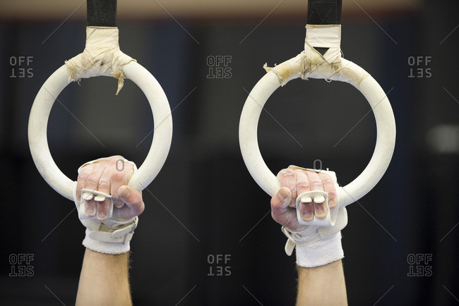 Gymnast's hands gripping the rings, cropped