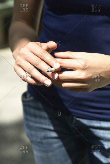 Woman holding lit cigarette, cropped