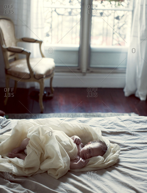 New born baby sleeping in bed in bedroom