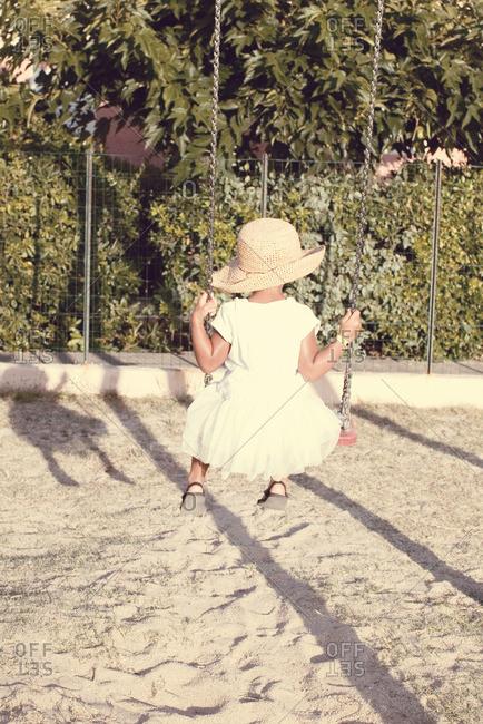 Little girl sitting on swing, rear view