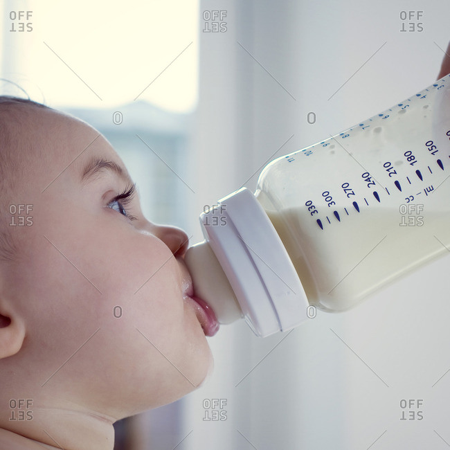 Infant drinking milk from bottle, side view