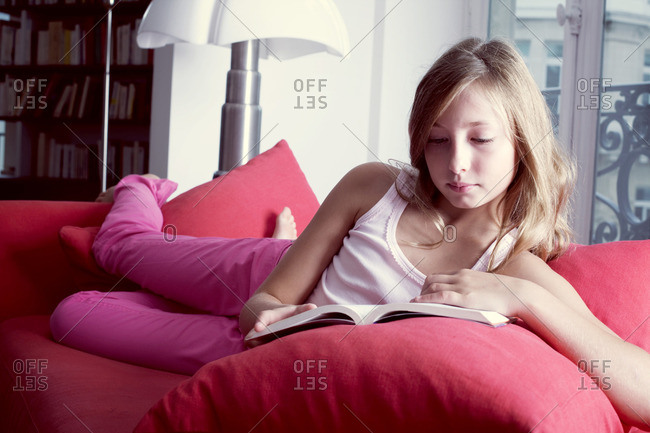 Girl reclining on couch reading book