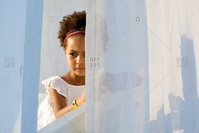 Little girl looking through curtain, portrait