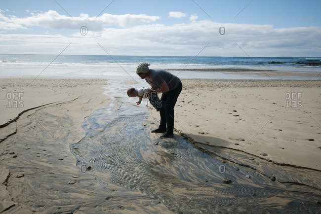 Father and toddler looking at rippled sand at the beach
