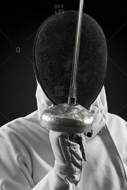 Fencer holding up foil, portrait