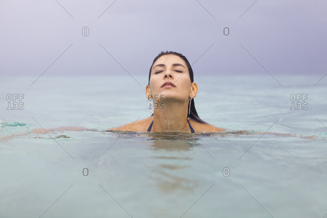 Young woman in water with eyes closed