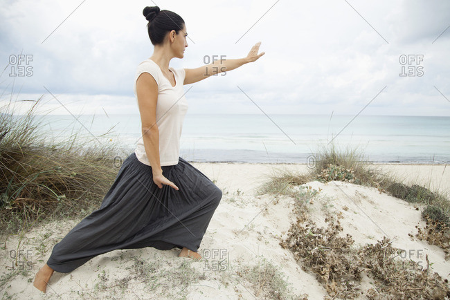 Woman practicing tai chi chuan on beach, side view
