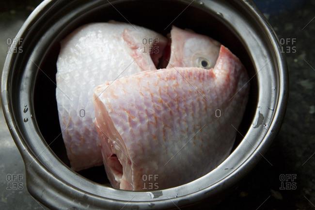 Chopped raw fish in pot