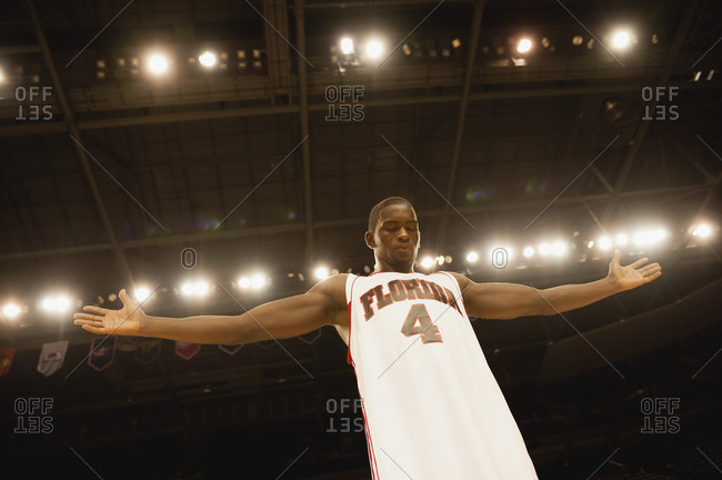 Basketball player standing with arms out, low angle view