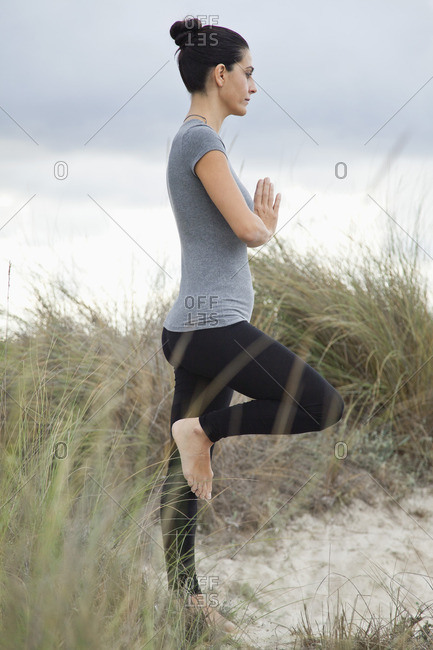 Mature woman in tree pose on beach, side view