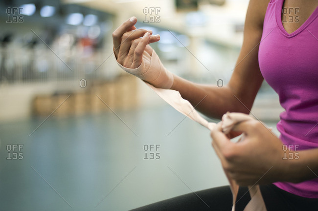 Woman wrapping hand with bandage, cropped