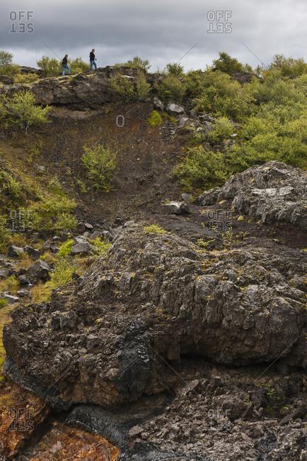 Tourists walking along hillside of lava field, Iceland