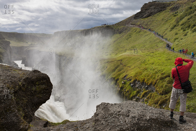 Tourist standing at edge of Gullfoss waterfall, Iceland